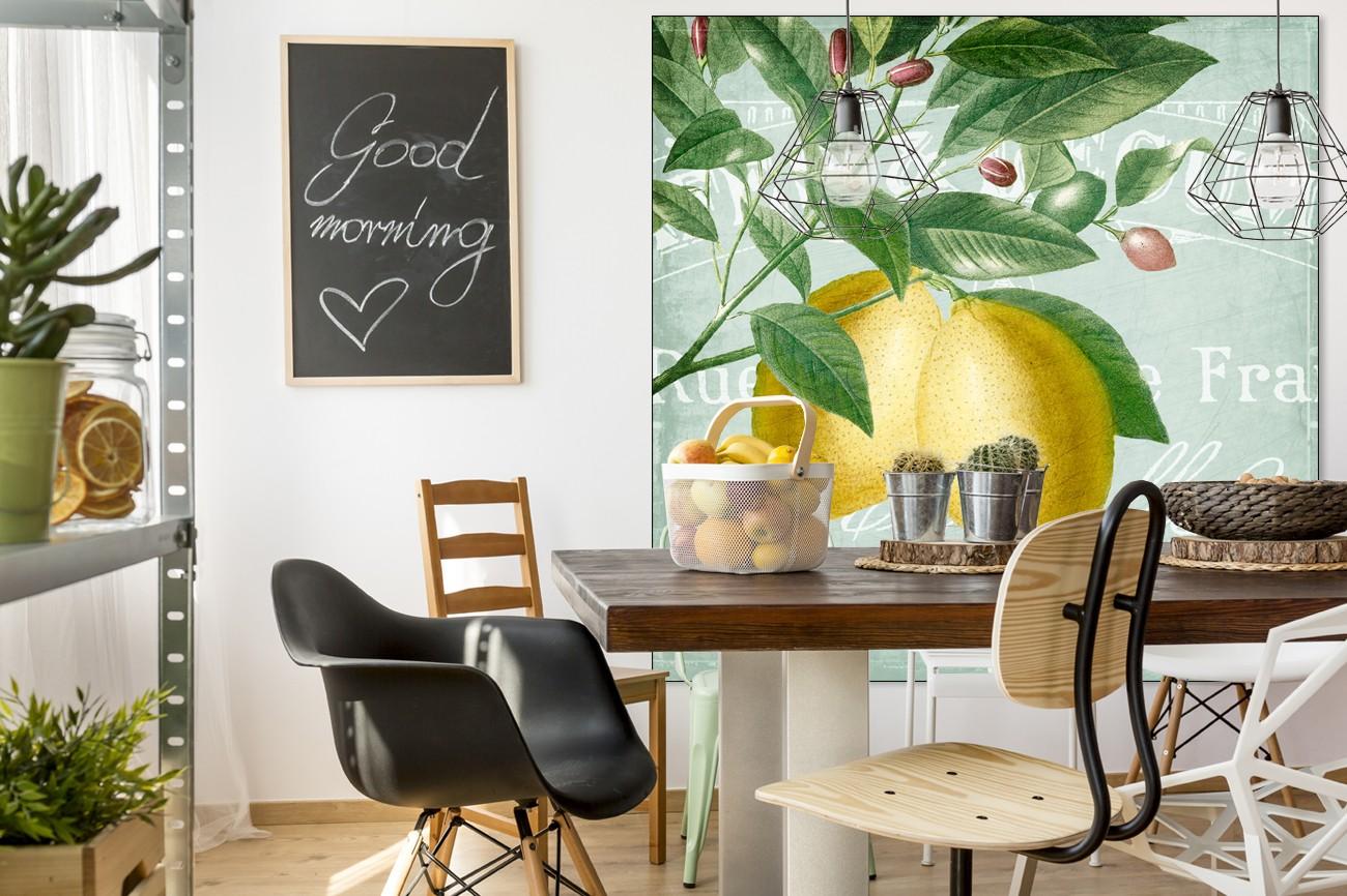 Schilderij met twee citroenen op de voorgrond aan bladeren en takken op een licht blauwe achtergrond van Kimberly Allen met als titel Lemon drop 2 op textieldoek.